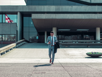 man in a suit walking out of a building