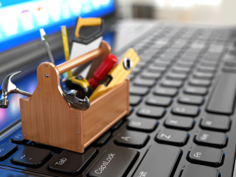 tiny toolbox sitting on a keyboard in front of a lit computer screen
