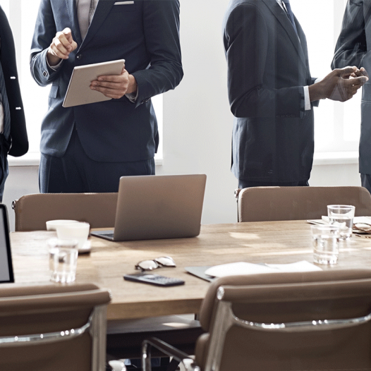 business executives standing around a conference room table shown from the shoulders down